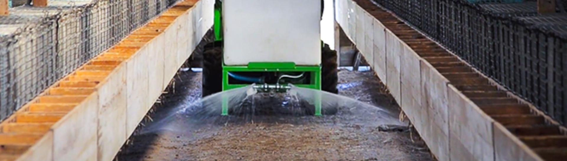 arbejdsbillede af Kalk- og vandspreder til avant minilæsser, billedet er på en minkfarm
