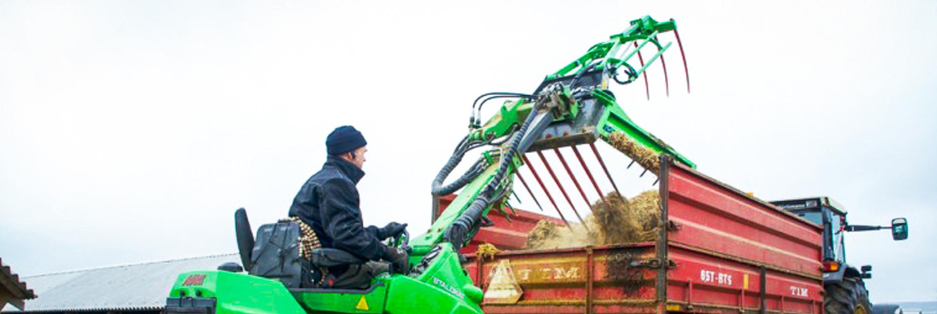 arbejdsbillede af et Klip-Klap Greb med overfald i brug på en AVANT på en minkfarm