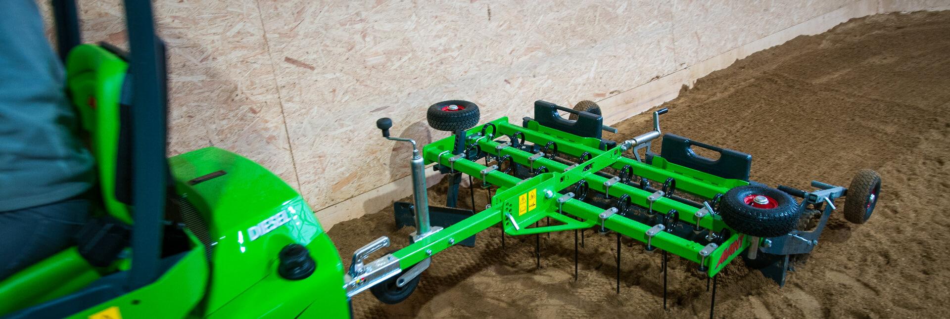 Arbejdsbillede af Ridebaneplaner 150, der harver en ridebane effektivt monteret på en avant minilæsser